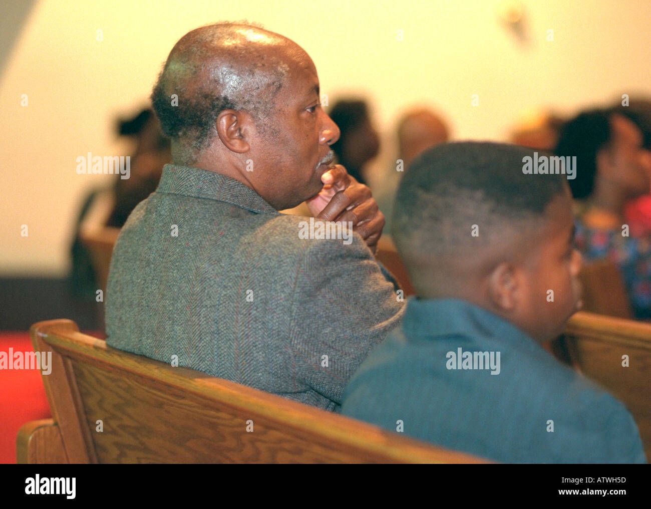 Black father and son ages 55 and 14 listening to sermon at church