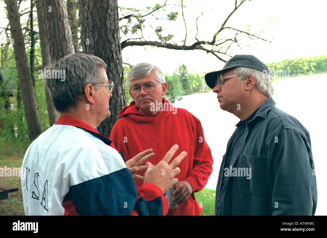 Friends ages 50 and 62 talking at men's encounter weekend at Roy Lake. Nisswa Minnesota USA - Stock Image