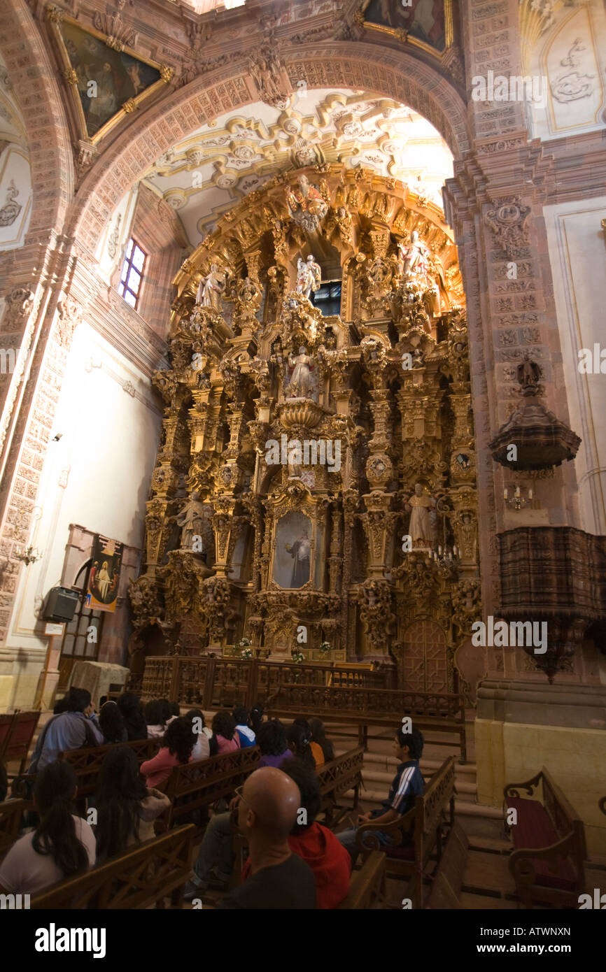 MEXICO Valenciana Gilded and elaborate retablos at altar tour group interior of Church of San Cayetano churrigueresque - Stock Image