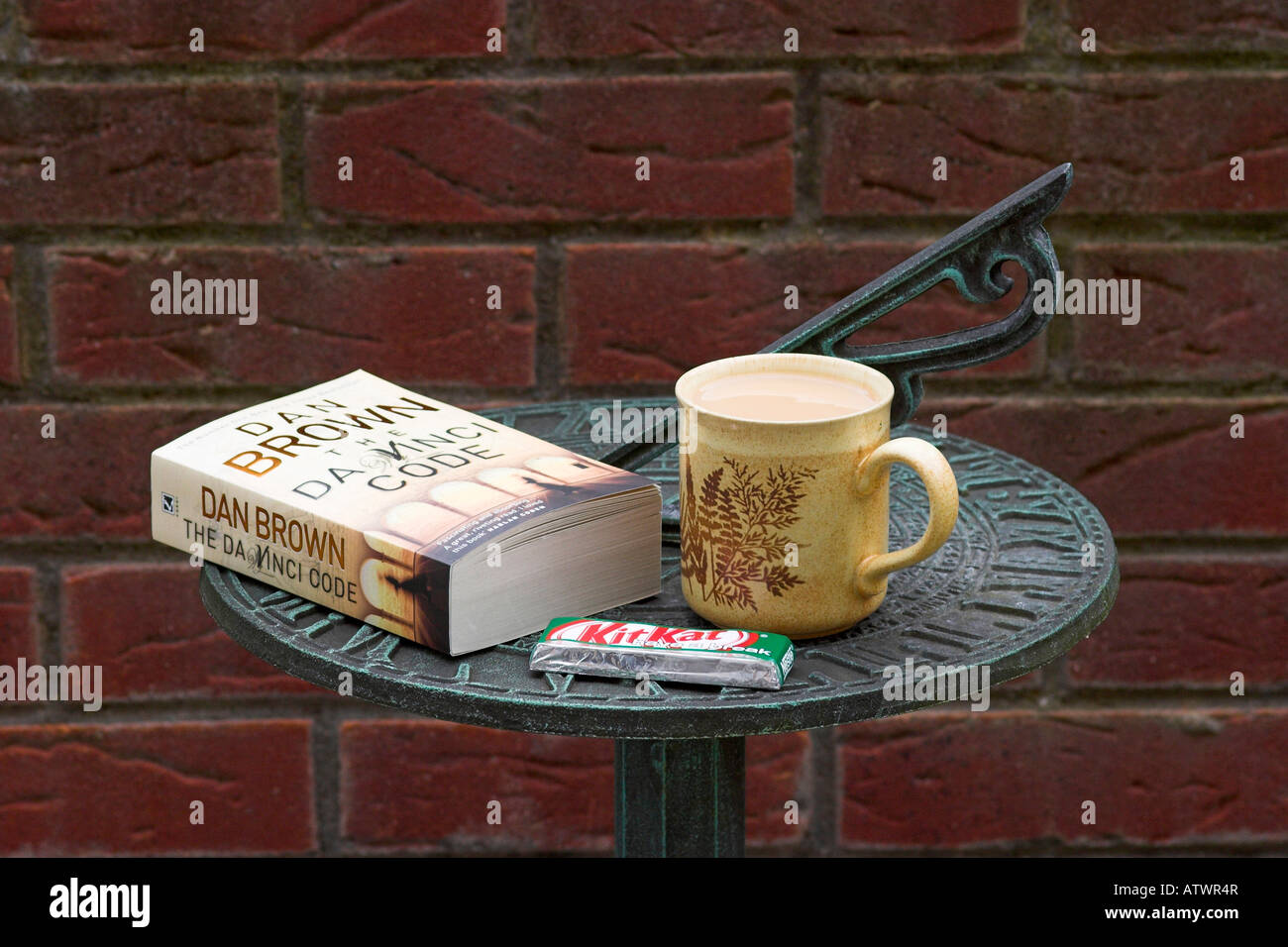 Break time.  A mug of tea, a Kit-Kat chocolate wafer and a copy of Dan Brown's The Da Vinci Code on sundial. - Stock Image