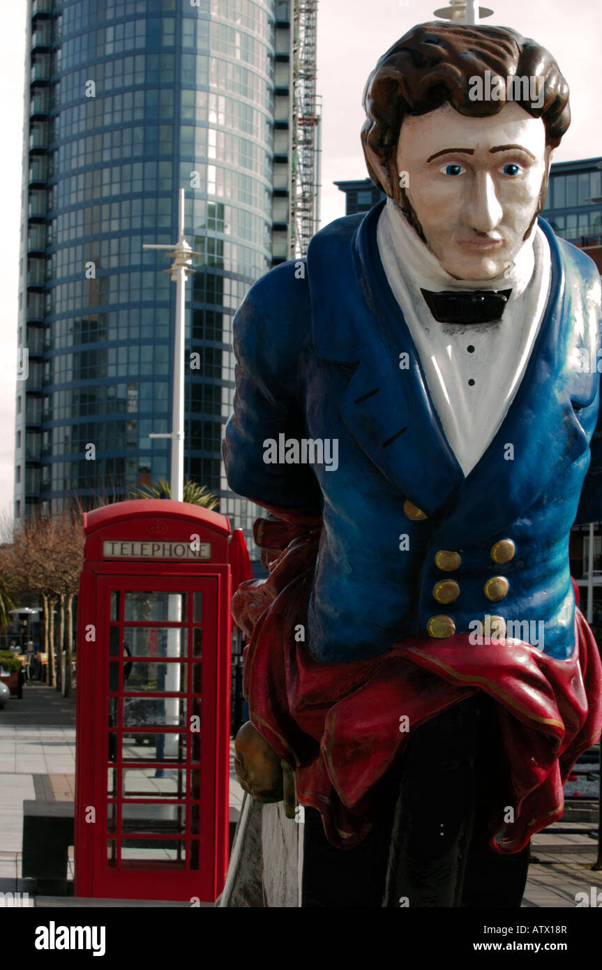 a figurehead and old style type red telephone box at gunwharf quays shopping centre on the waterfront at portsmouth - Stock Image