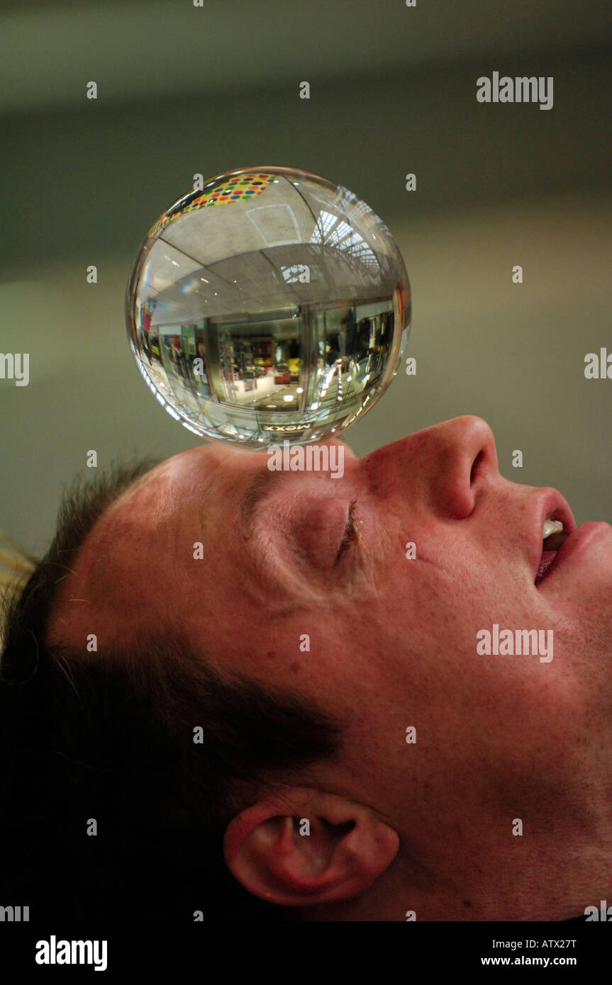 an illusionist street performer using looking into balancing on his forehead a crystal glass ball performing in - Stock Image