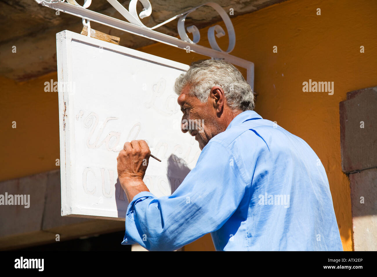MEXICO Valenciana Older Mexican man handpainting sign for store left handed - Stock Image
