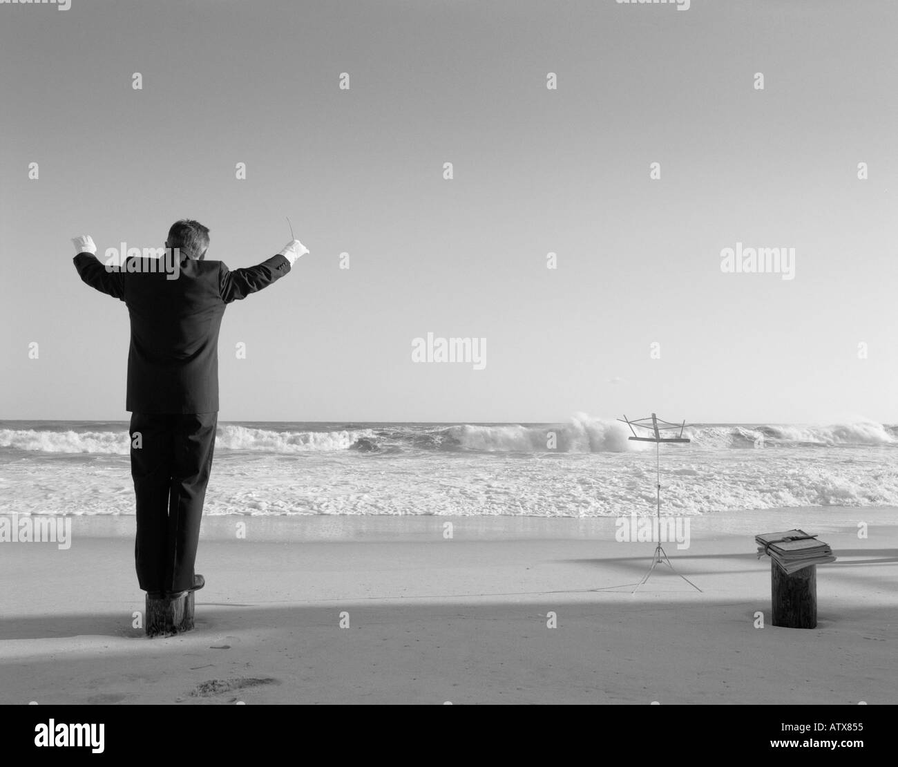 Man 40-44, 45-49, 50-54, 55-60, 60-65, 65-69, years old, conducting invisible orchestra at beach (rear view), Hamptons, New York, USA - Stock Image