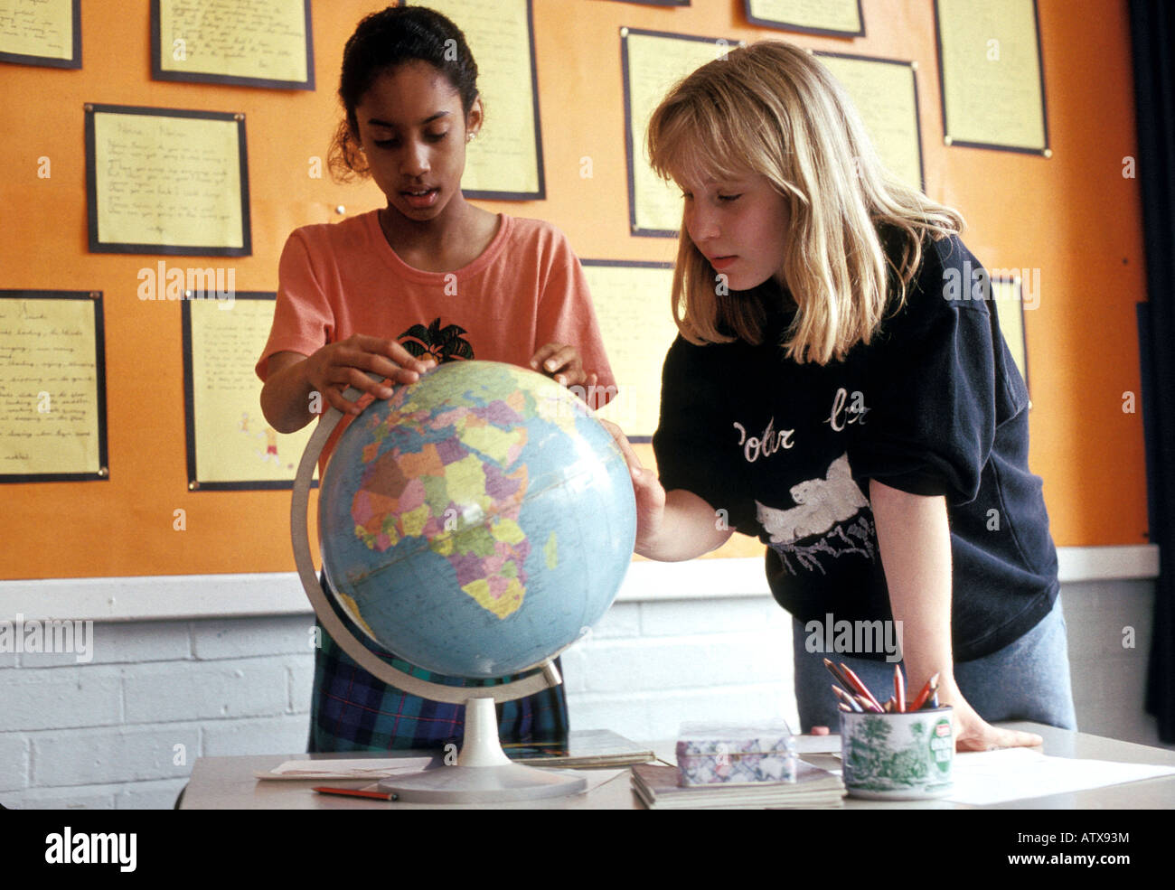Secondary school children learning geography by studying a world globe - Stock Image