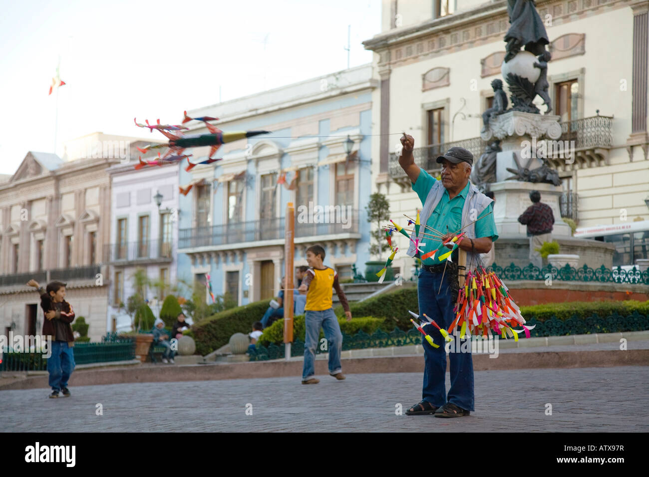 MEXICO Guanajuato Mexican man selling whirligig toys in Peace Plaza Plaza de la Paz spinning toys on string in air Stock Photo