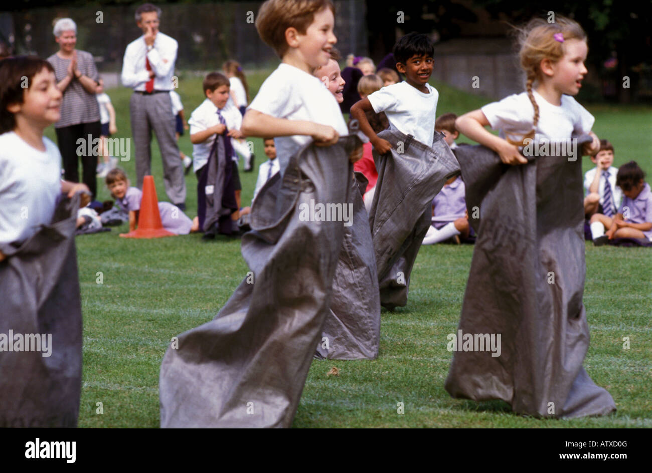 Children taking part in Sports day sack race at end of year sports day - Stock Image