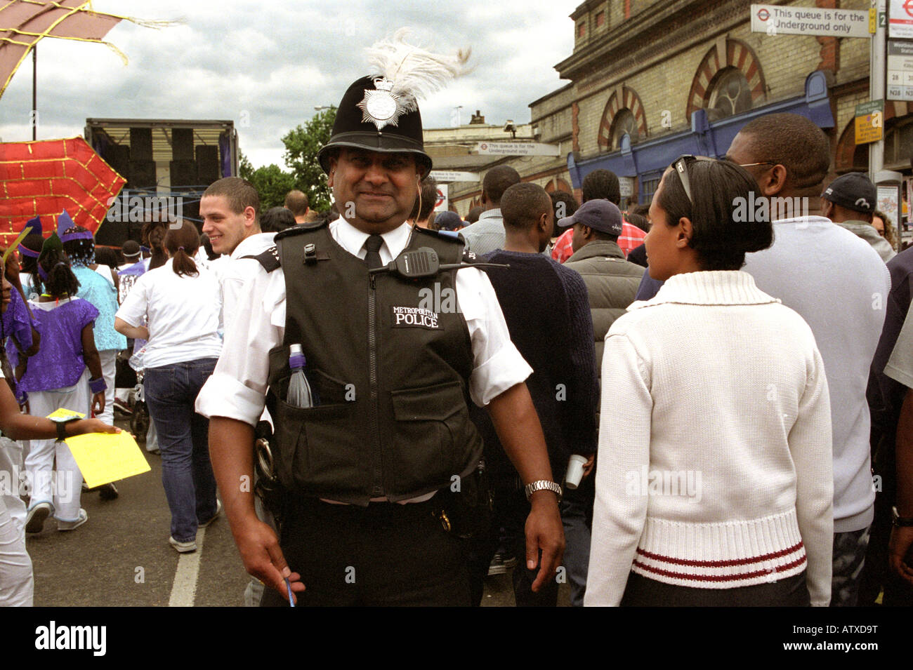 A police officer at the Notting Hill Carnival with a feather in his hat. - Stock Image