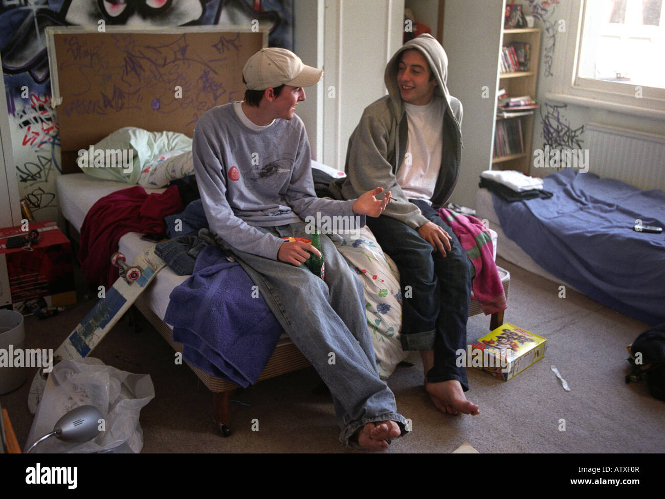 Two teenage friends smoking drinking and chatting in bedroom. Stock Photo