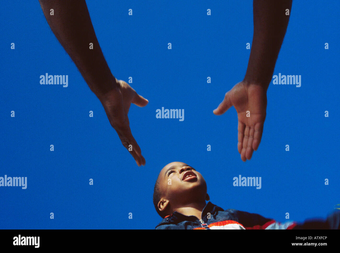 7 year old African American boy leaping into father's hands - Stock Image
