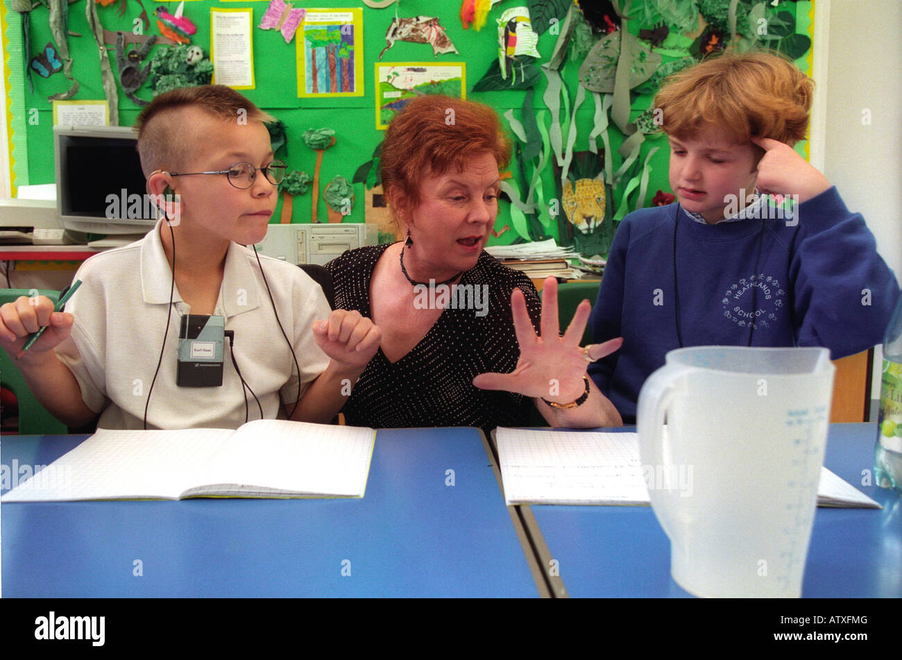 Female teacher working with deaf children in a special school. - Stock Image