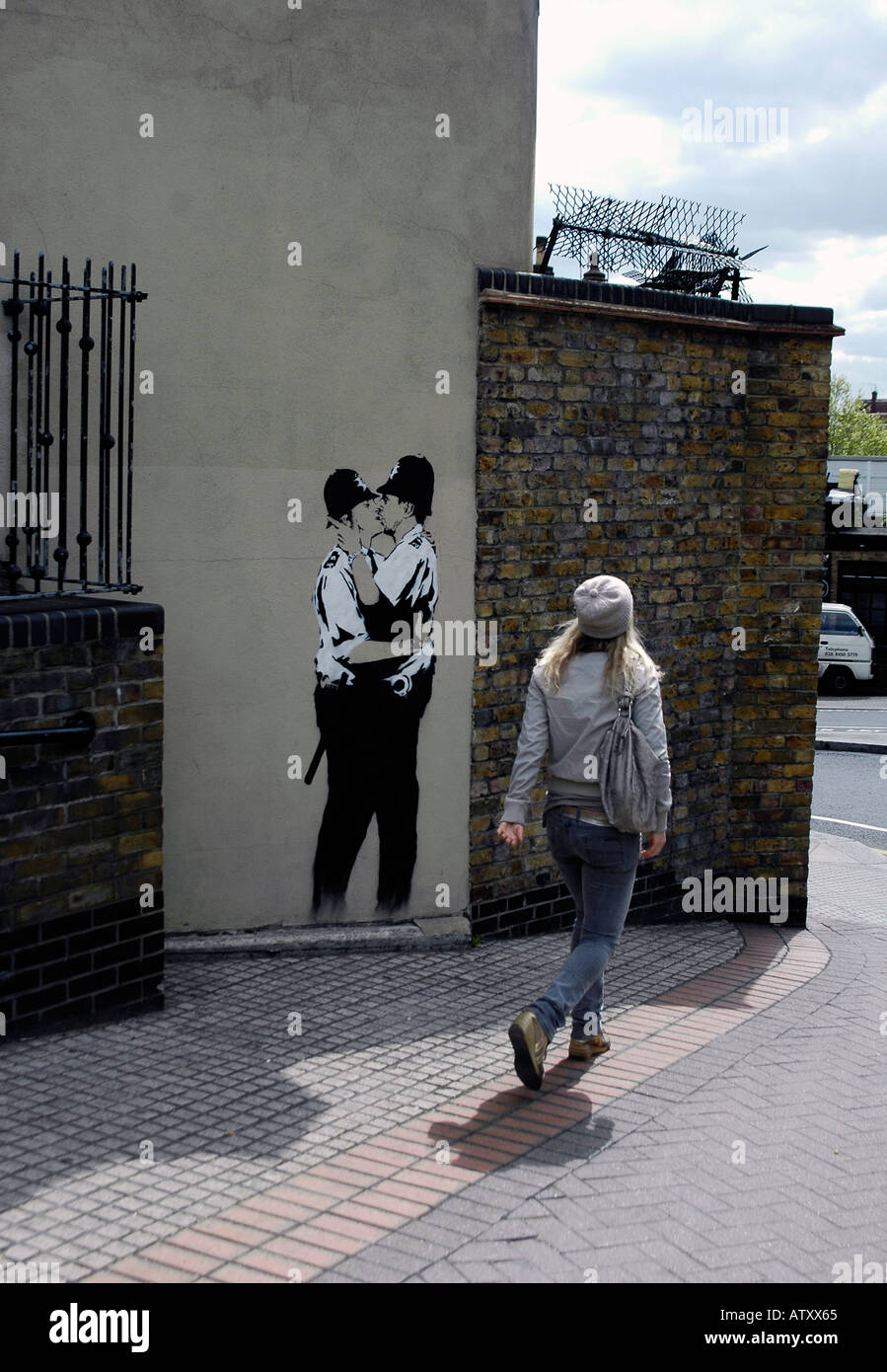 since removed Banksy kissing Policemen in Ladbroke Grove with passing person Stock Photo