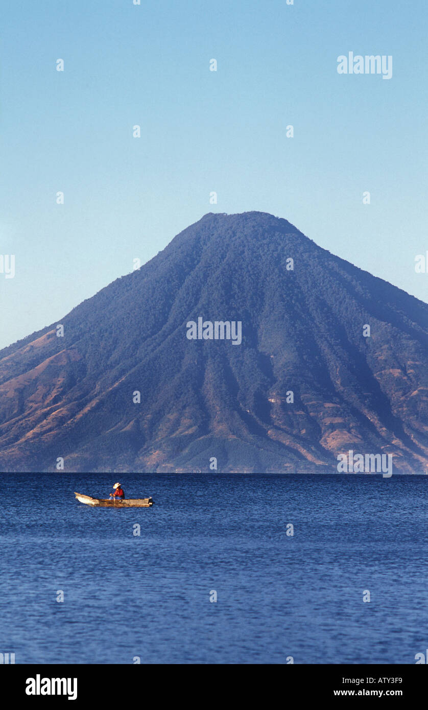 Fisherman from Santiago Atitlan in a canoe beneath the towering peak of San Pedro Volcano Lake Atitlan Dept Solola Guatemala - Stock Image