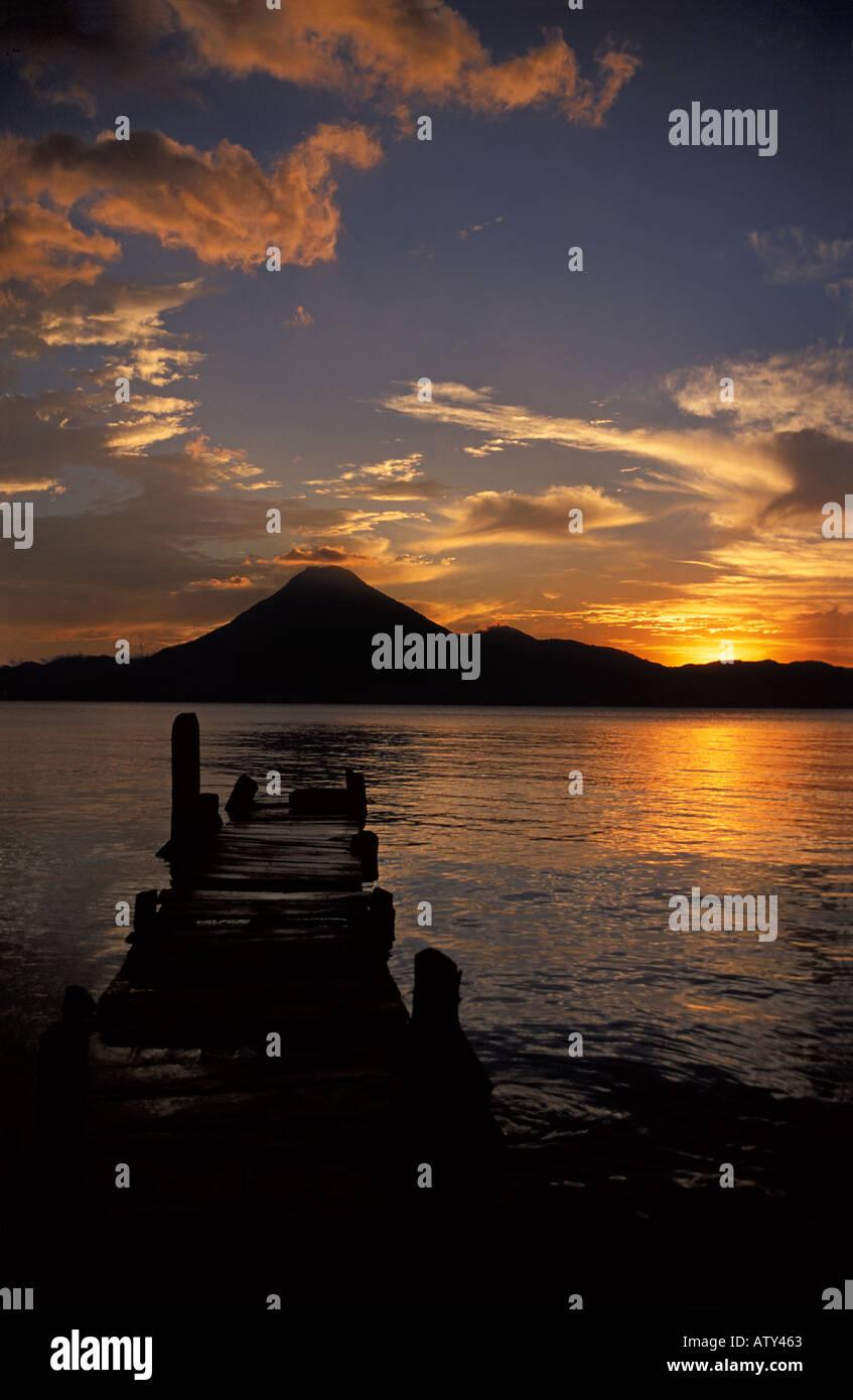 Boats and jetty silhouetted at sunset Panajachel Lake Atitlan Guatemala San Pedro volcano beyondStock Photo