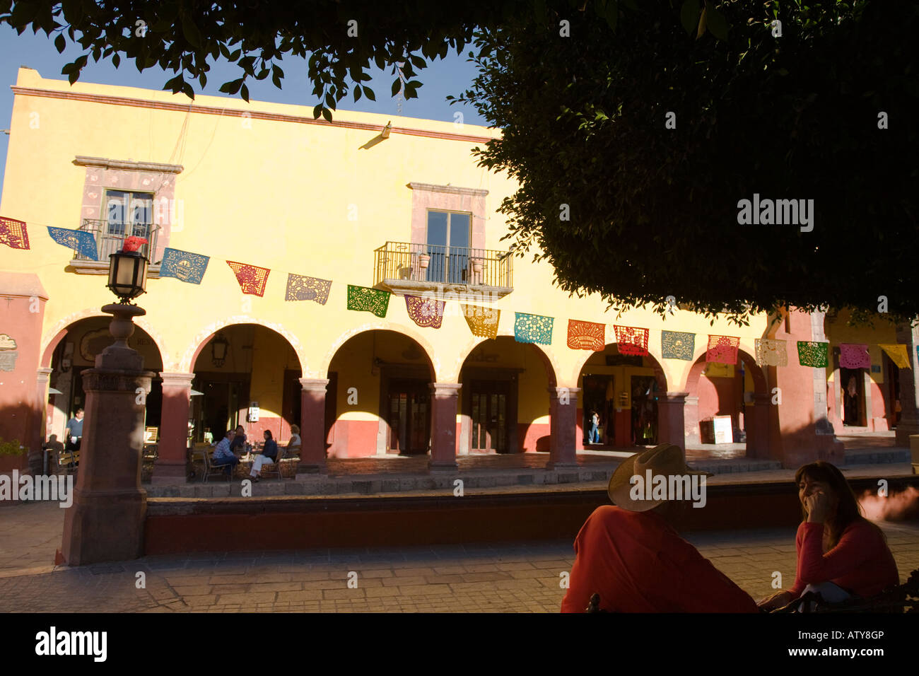 MEXICO San Miguel de Allende Cut out paper flags decorate plaza around El Jardin couple sitting on bench talking - Stock Image