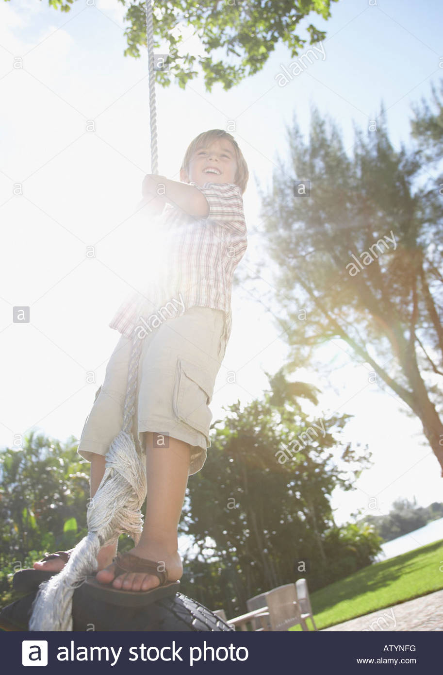 Young boy outdoors at park playing on tire swing - Stock Image