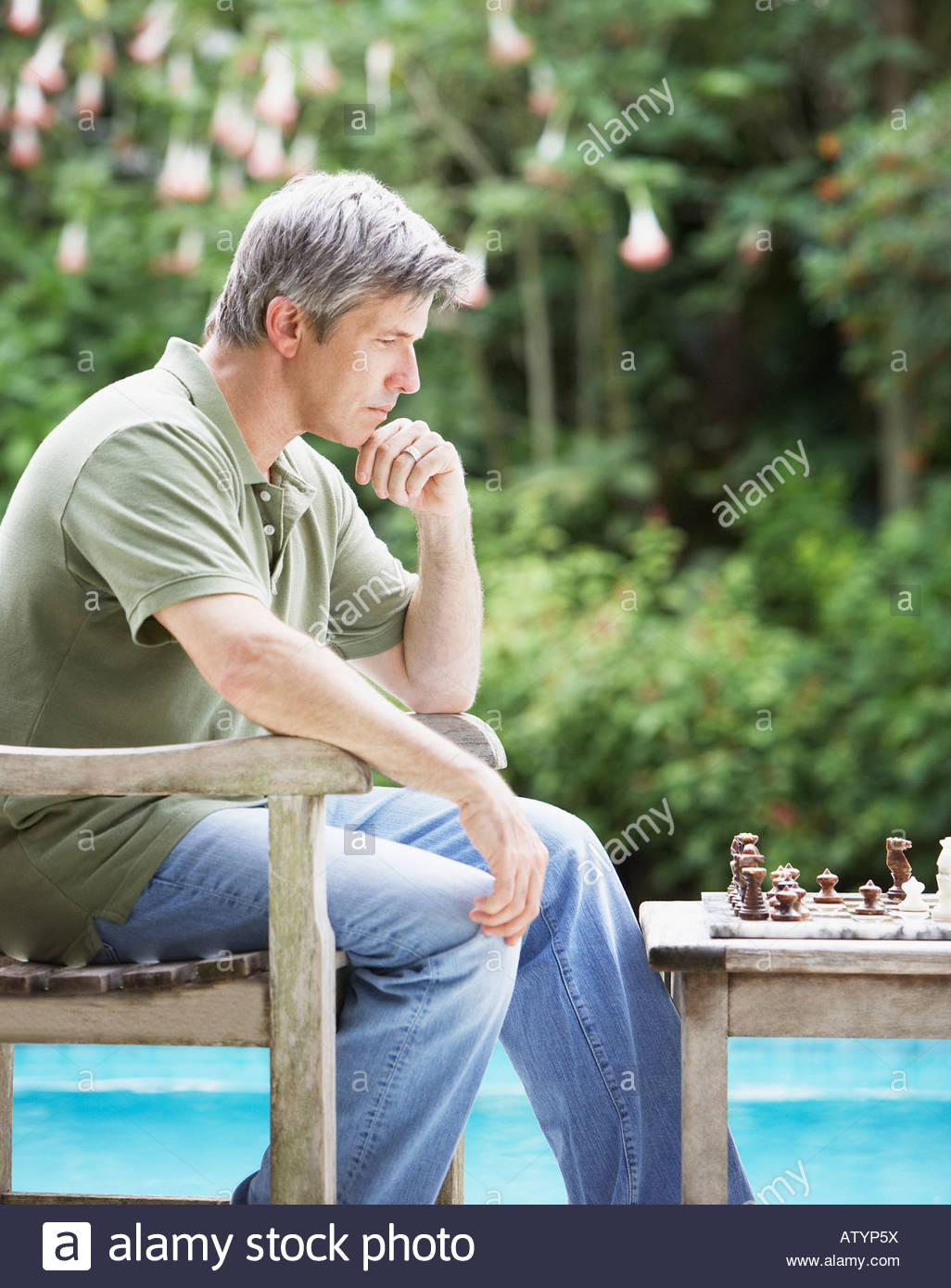 Man outdoors playing chess by swimming pool - Stock Image