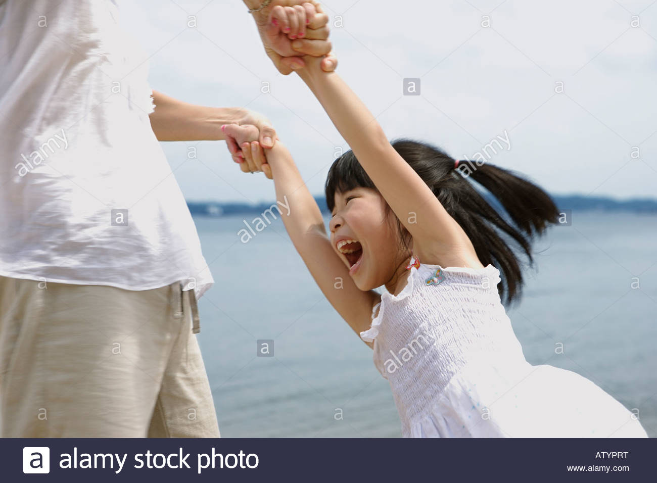 Woman and young girl playing outdoors on beach Stock Photo