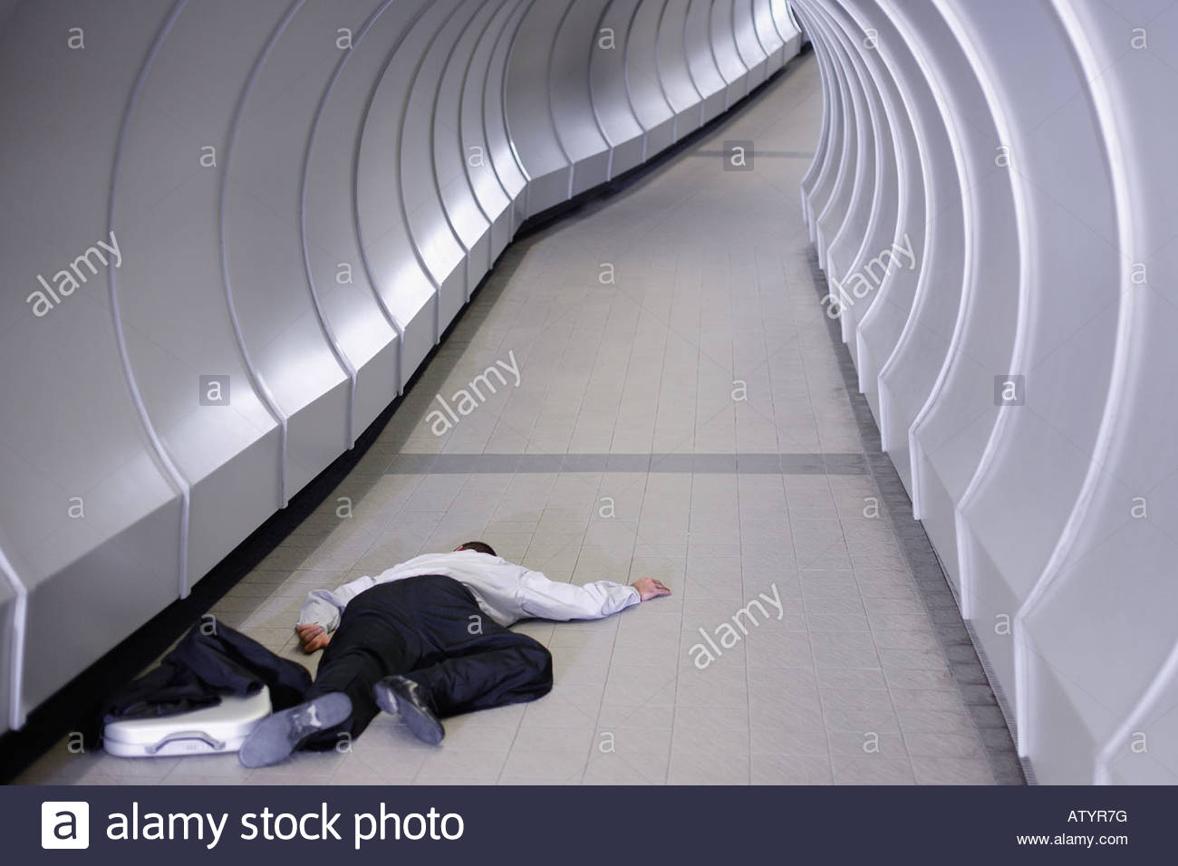 Businessman passed out in corridor - Stock Image