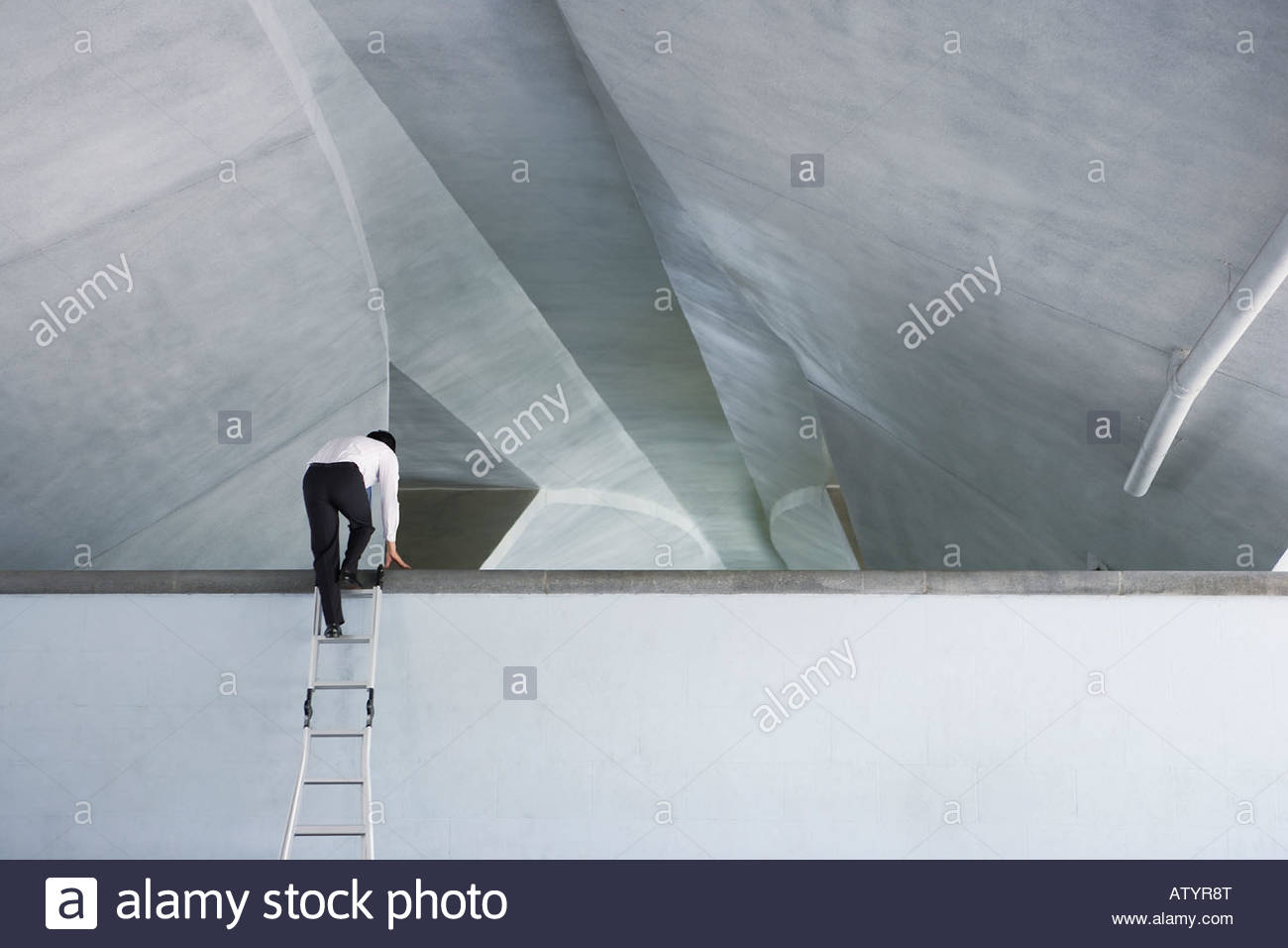 Businessman indoors using ladder to climb over structure - Stock Image
