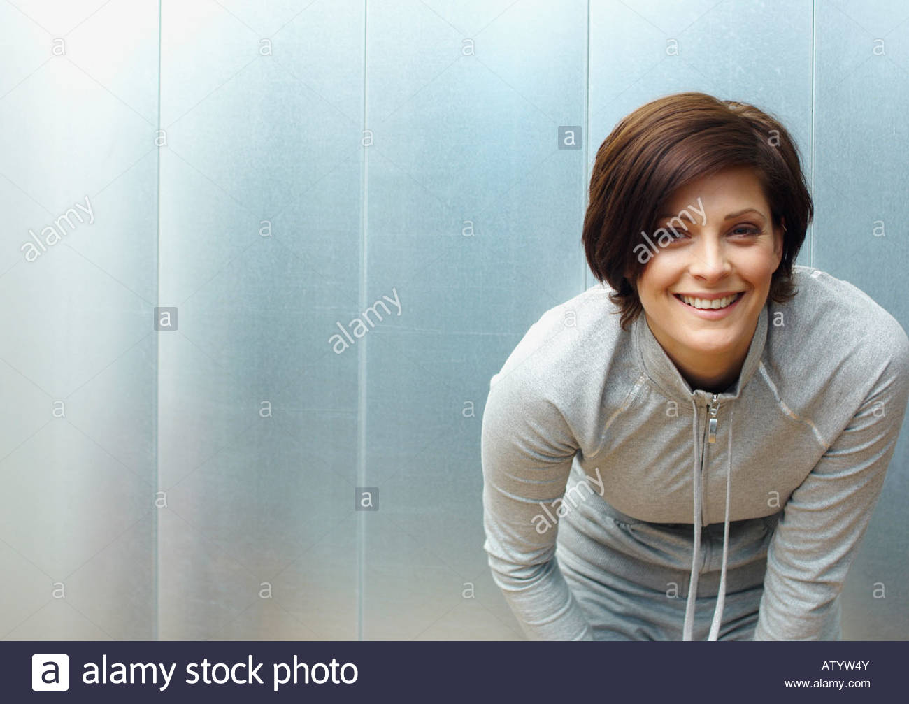Woman bent over in a locker room looking at camera - Stock Image