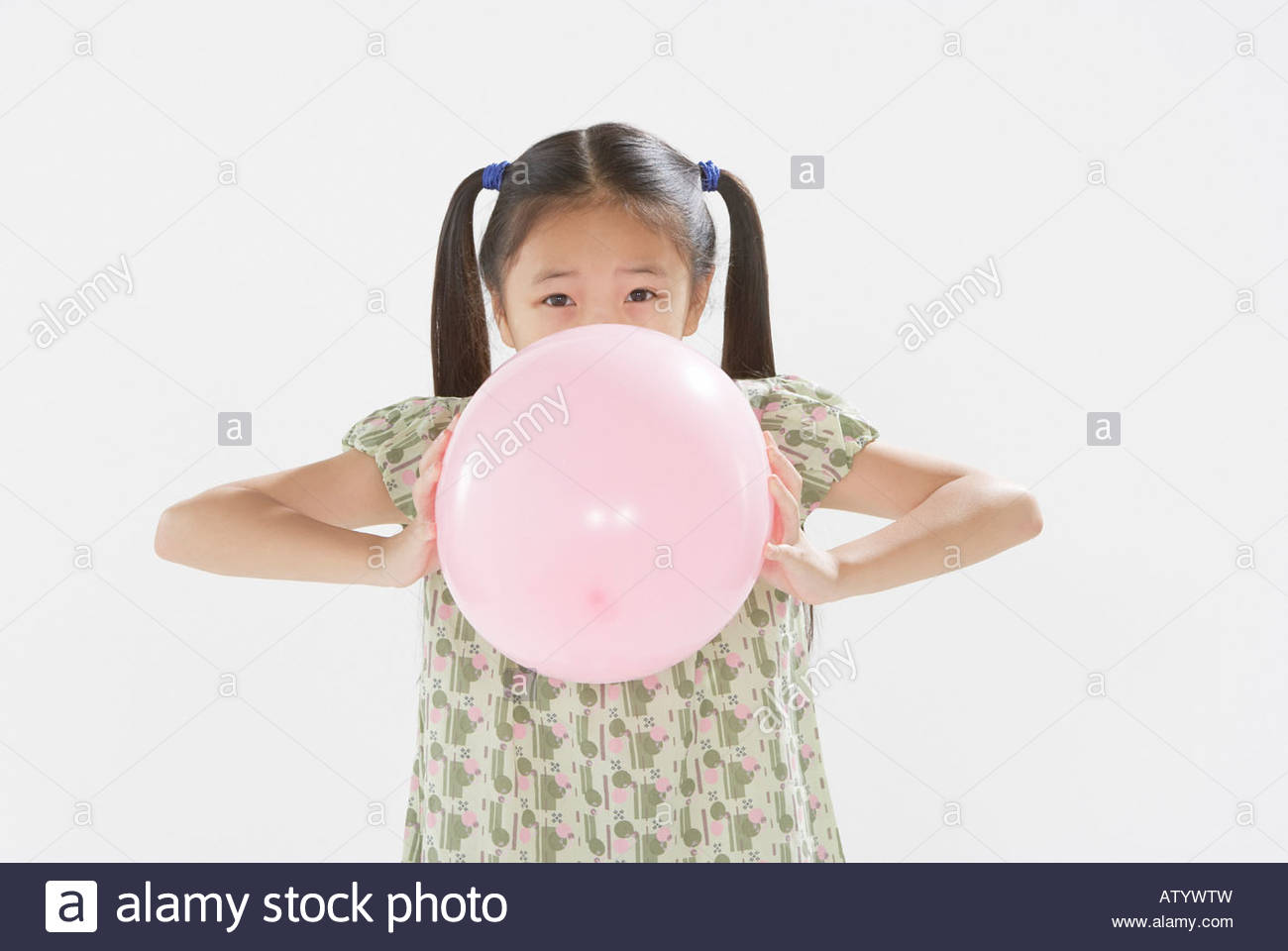 Young girl blowing up balloon indoors - Stock Image