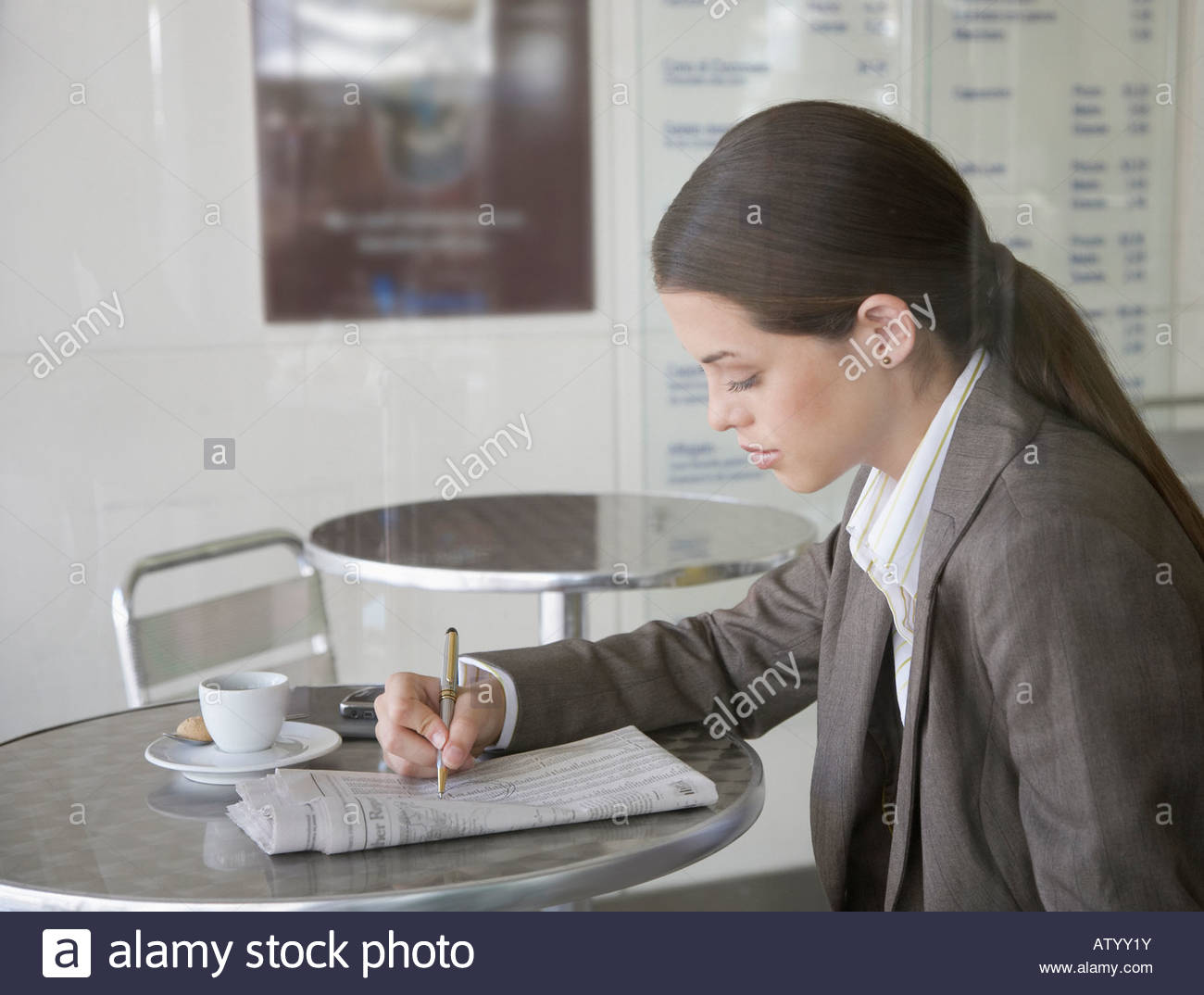 Businesswoman in cafeteria with newspaper - Stock Image