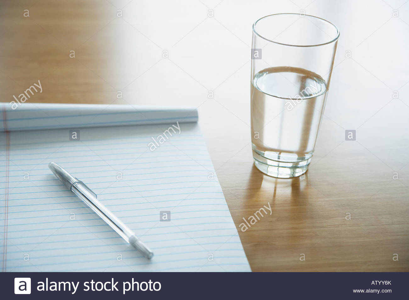 Notepad with a pen lying on it and glass of water on a table - Stock Image