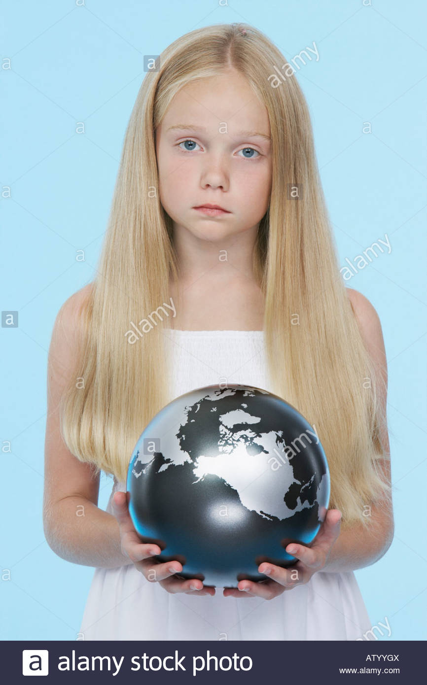 Young girl indoors holding silver globe - Stock Image