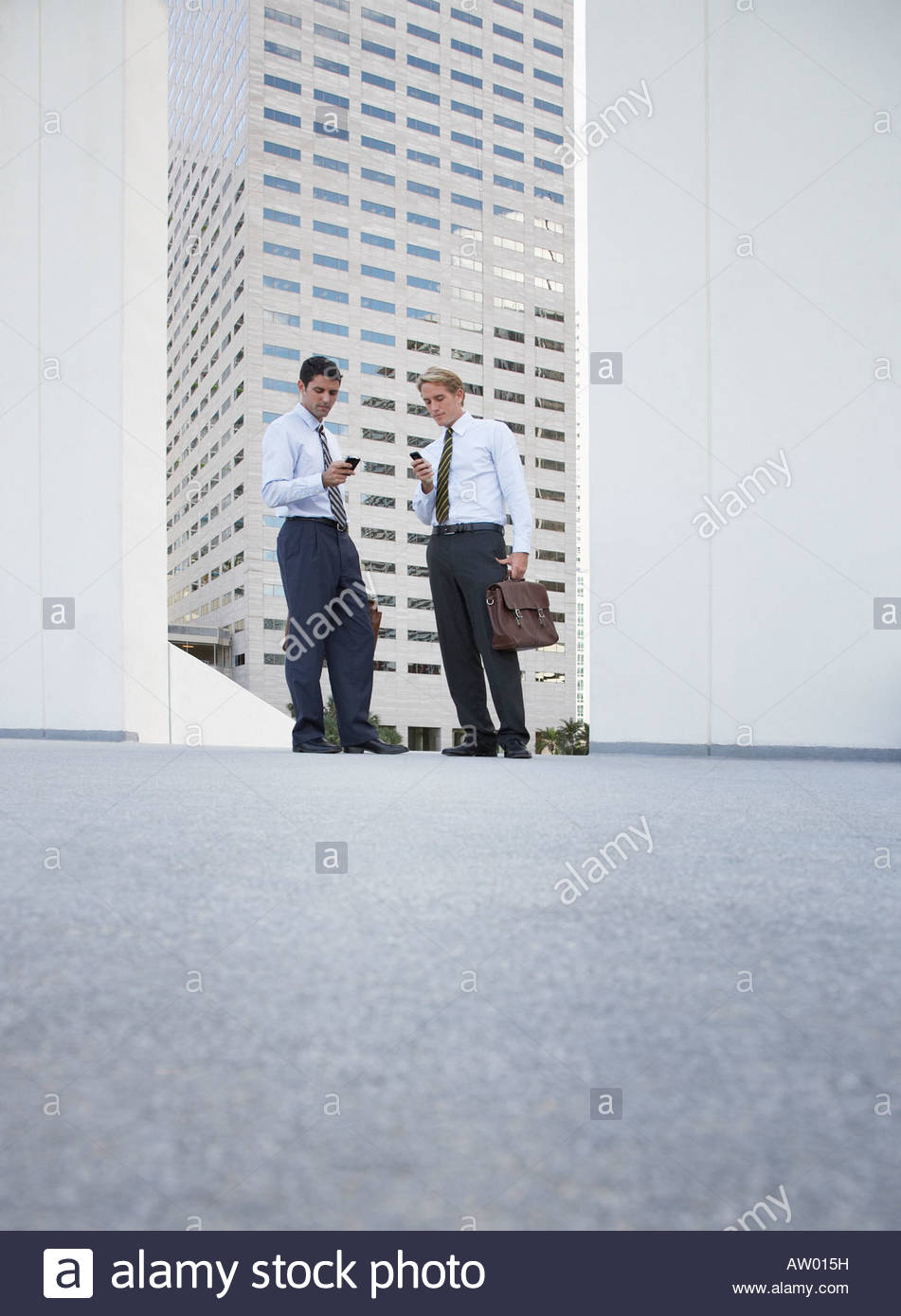 Two businessman standing outdoors looking at their mobile phones - Stock Image