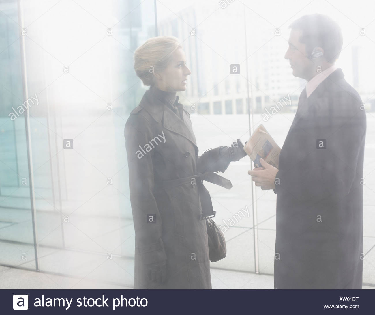 Two businesspeople talking by a door - Stock Image