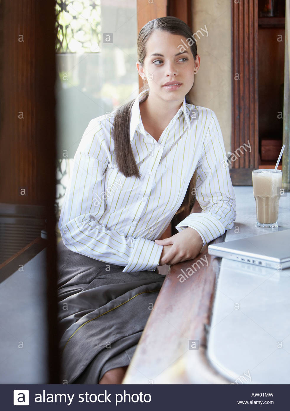 Businesswoman sitting at bar with laptop - Stock Image