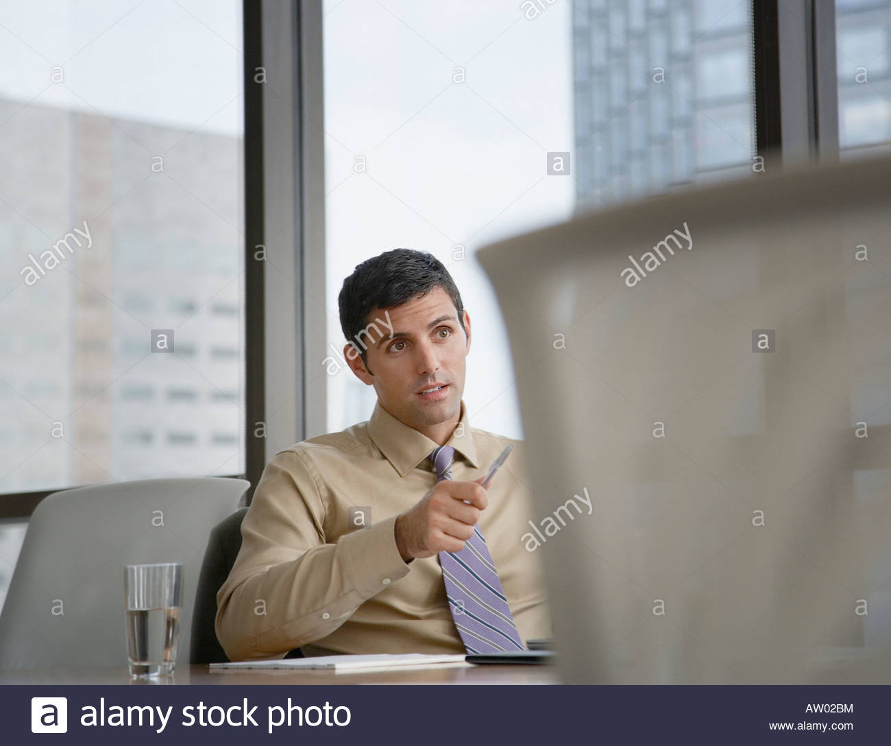 Businessman in boardroom pointing his pen at something - Stock Image