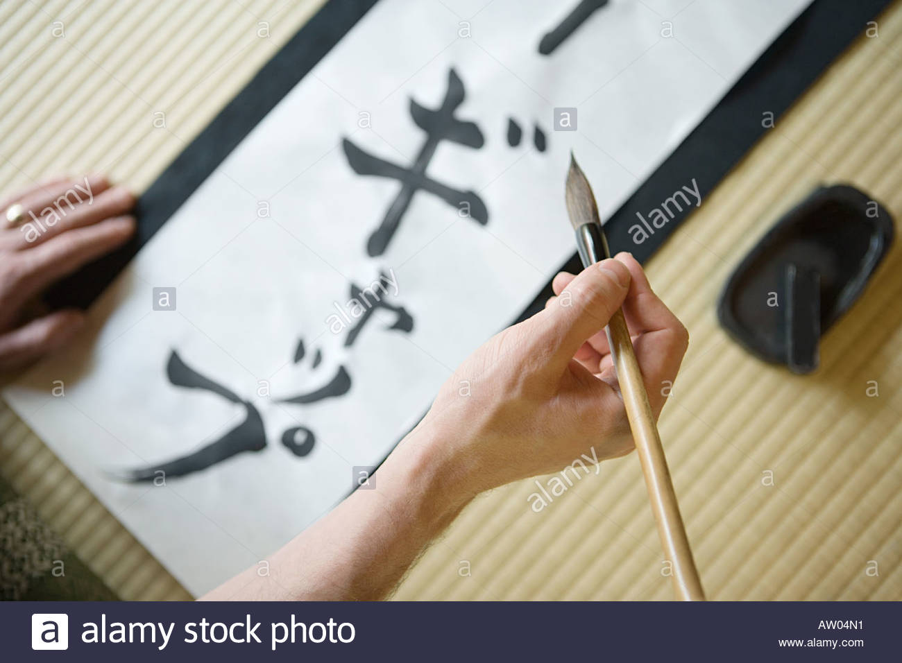 Man writing in japanese script - Stock Image