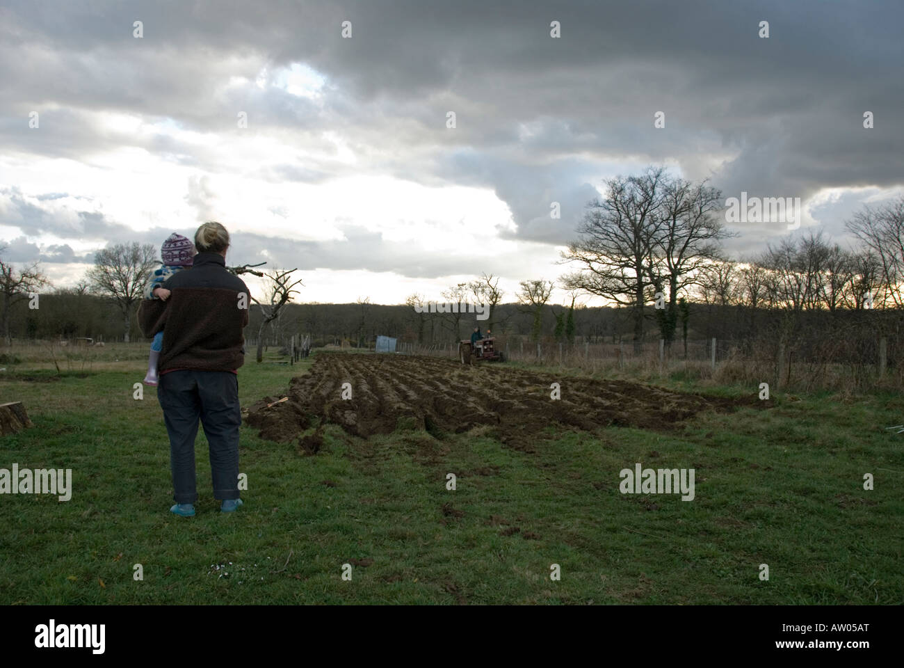 Stock photo of a mum holding her daughter watching their smallholding being ploughed - Stock Image