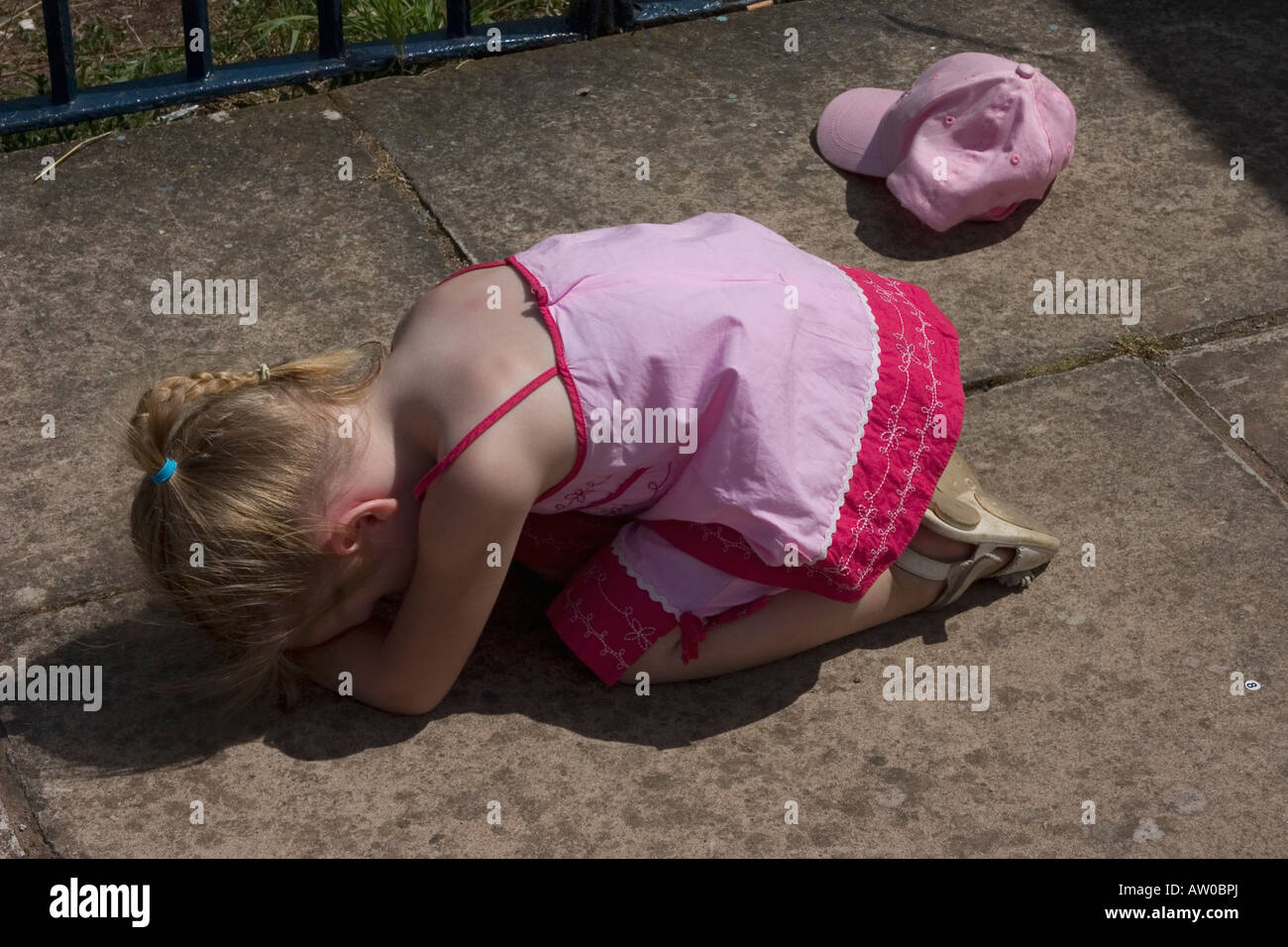 Young girl throwing off hat and having a tantrum. - Stock Image