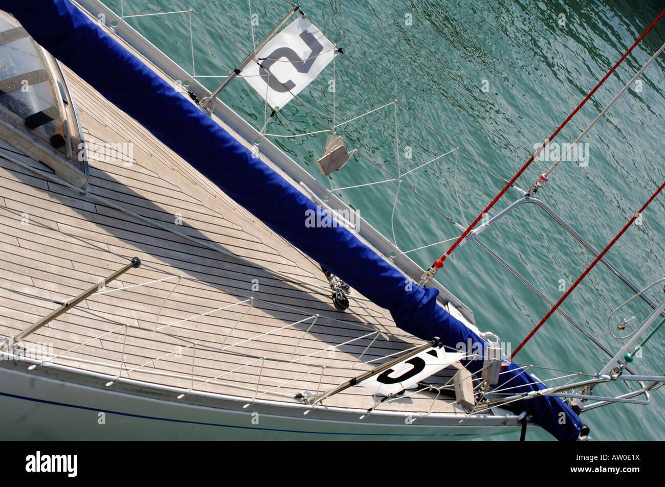 the bow foredeck of a large fast racing yacht in a marinas showing spinaker boom lying on wooden planked deck and - Stock Image