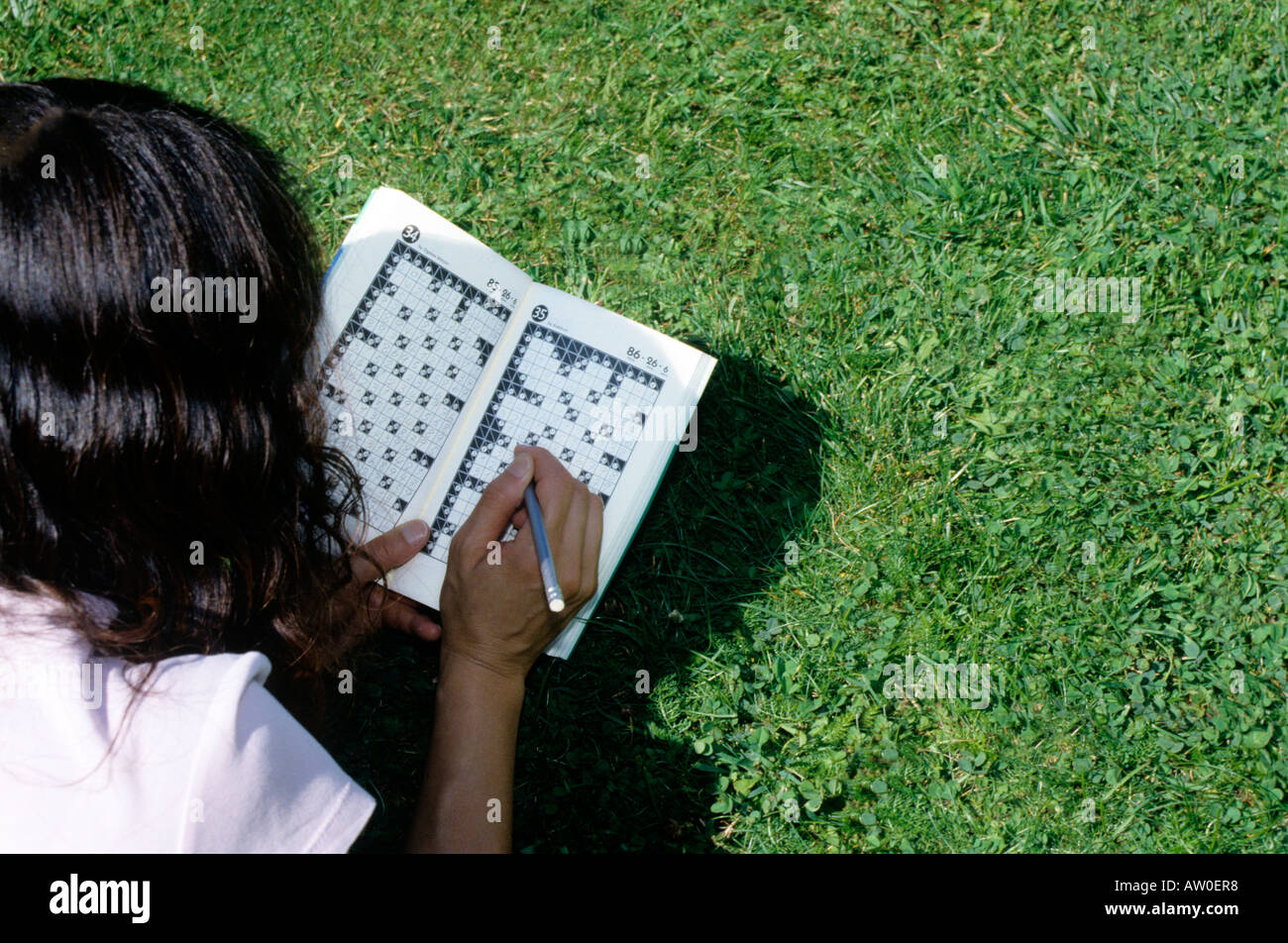 rear view of woman solving kakuro crossword - Stock Image