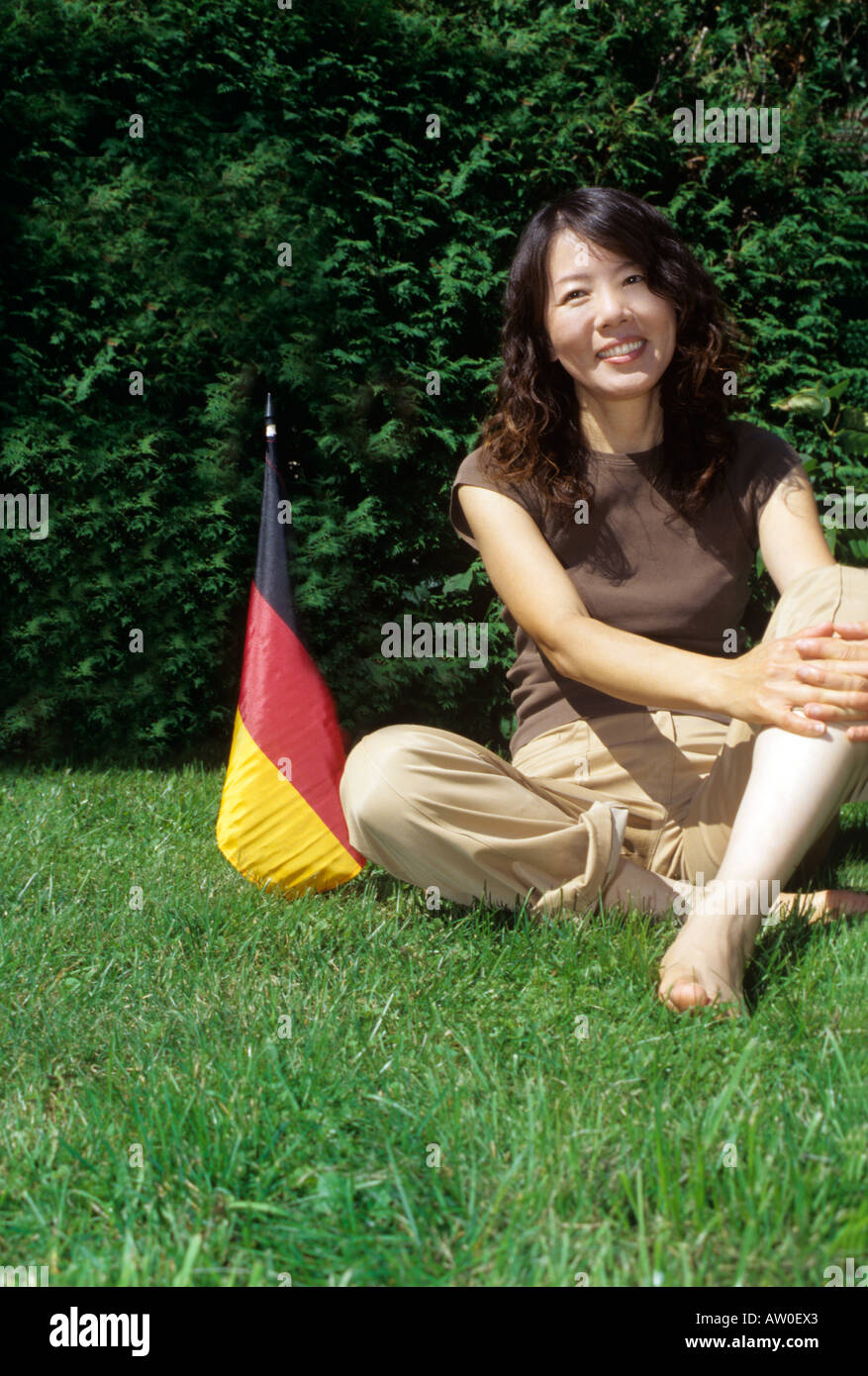portrait of smiling japanese woman sitting beside german flag in garden - Stock Image