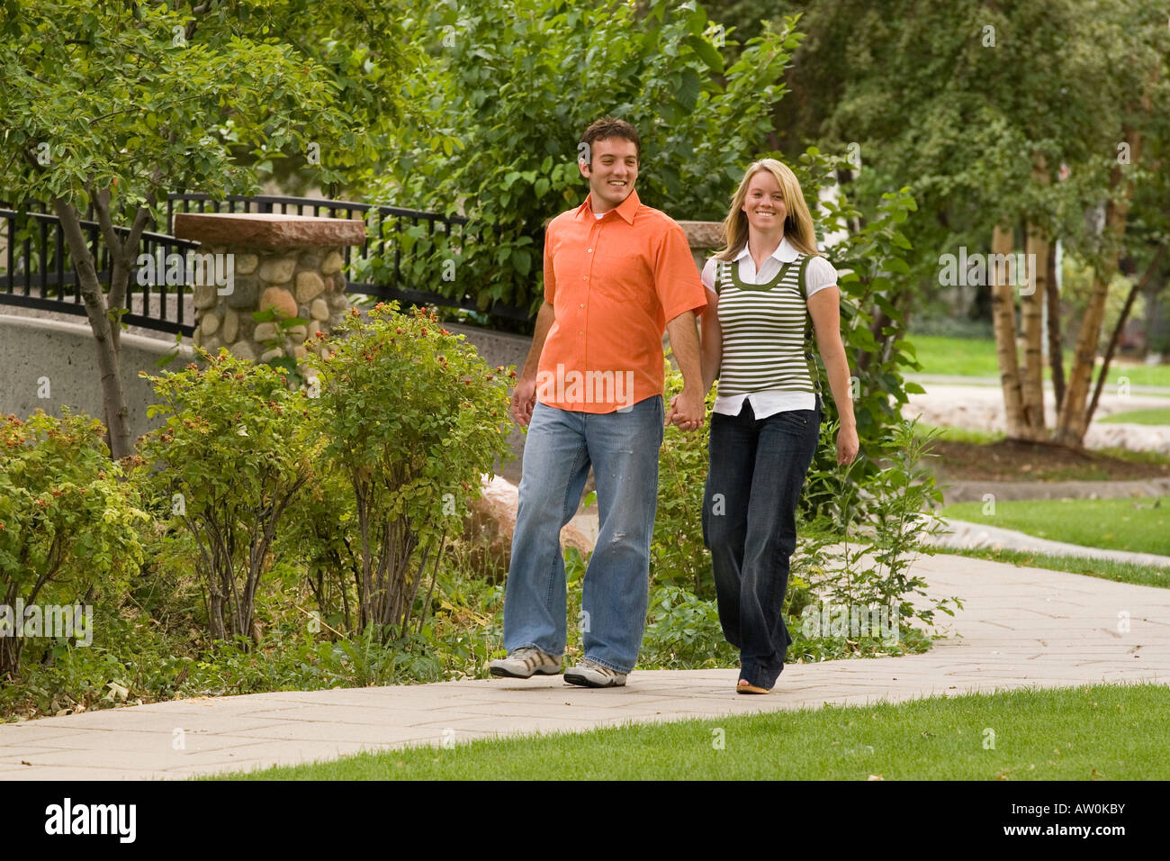 Young couple enjoying a walk in the park - Stock Image