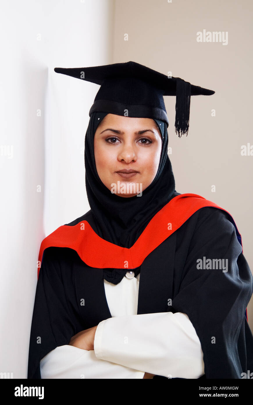 Portrait of Muslim woman wearing graduation cap and gown arms folded ...