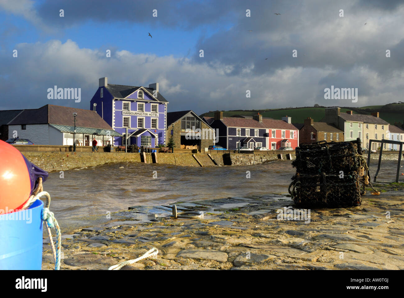 Aberaeron, Wales, showing a swell flowing into the harbour on a windy day - Stock Image