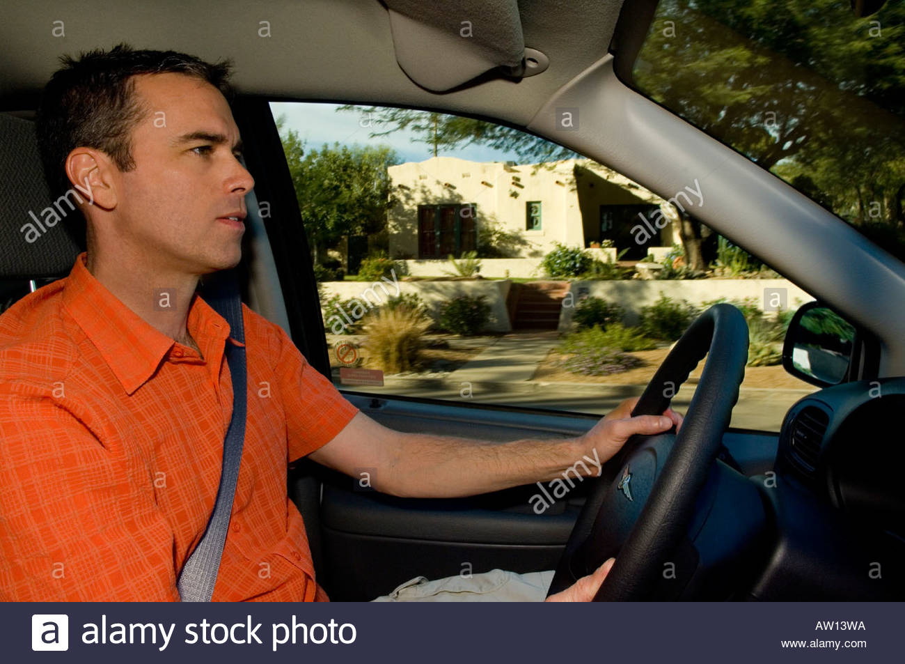 35 to 45 year old male man driving 2007 Chrysler, Town and Country, Minivan through Tucson residential  neighborhoods - Stock Image