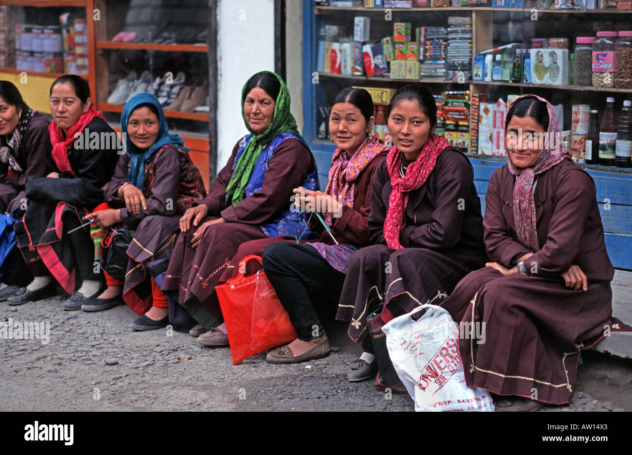 A row of friendly women in Himachal Pradesh foothills of the Himalayas waiting for transport Keylong town India Stock Photo