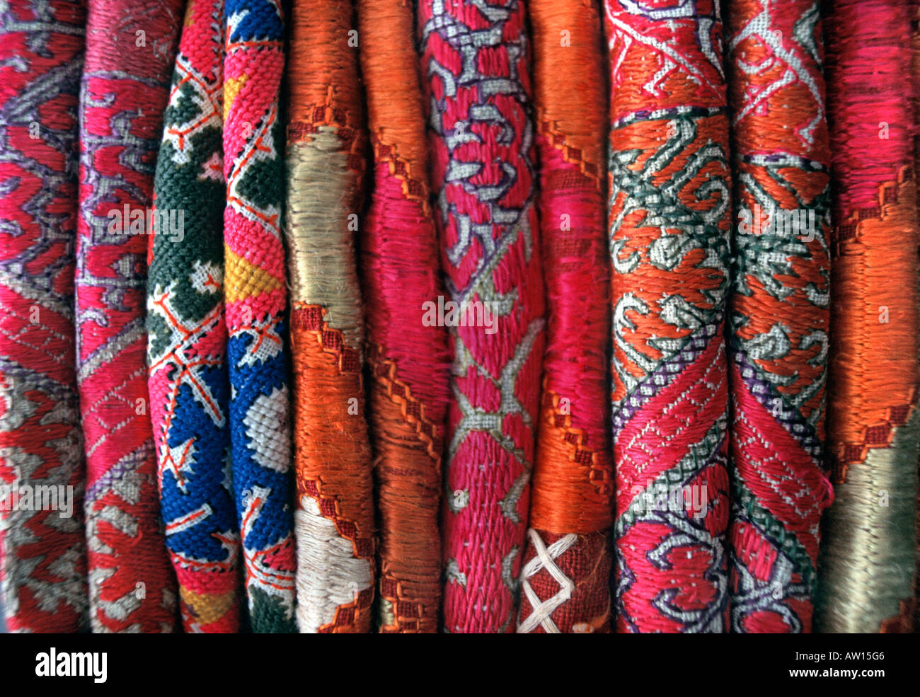 Stack of everyday and ceremonial hand embroidered silk and woven fabrics from Pakistan - Stock Image