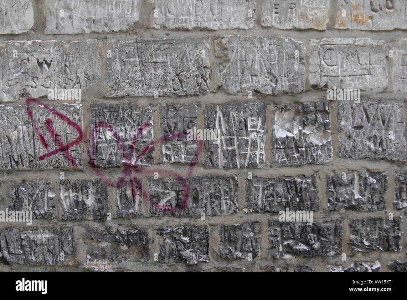 Grafitti carved into and sprayed upon an ancient chalk stone wall, Cheam, south London, Surrey, England - Stock Image