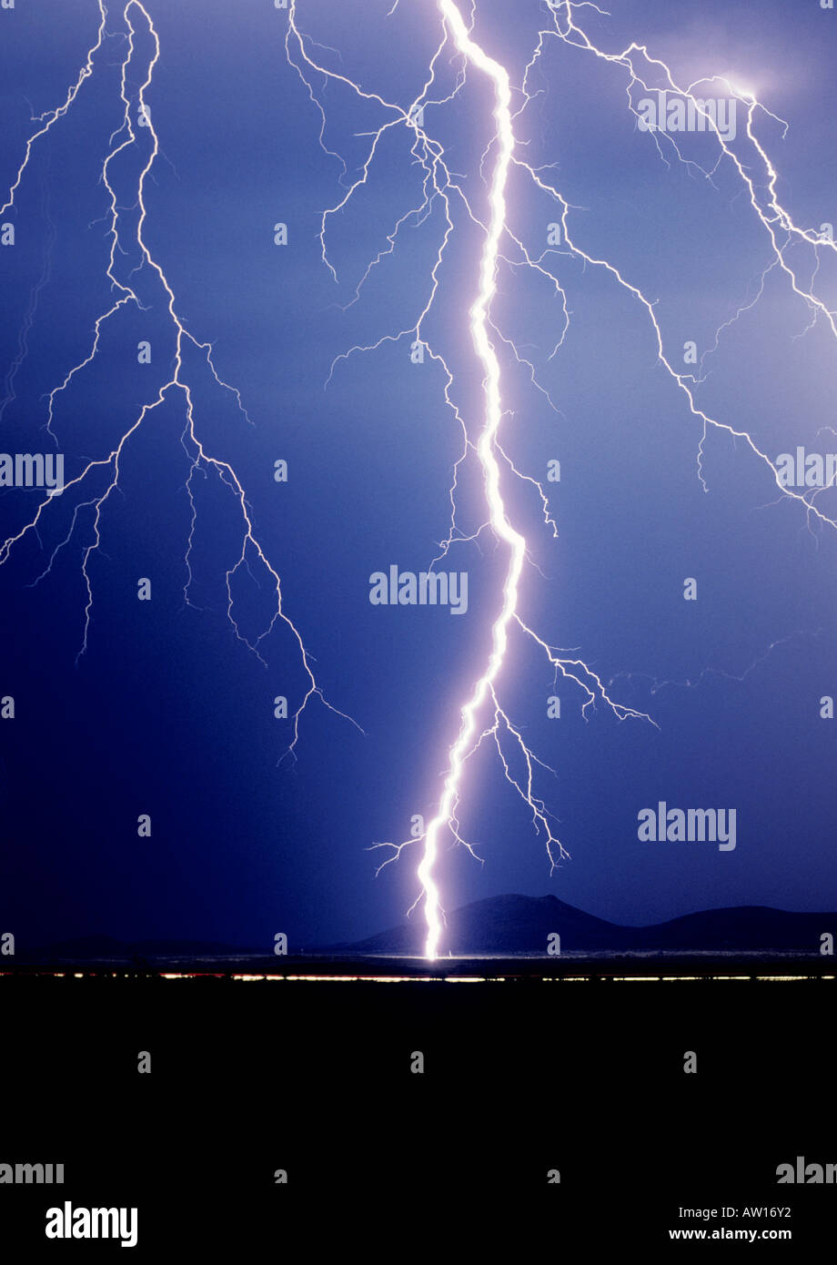 Cropped shot of a huge singular lightning bolt striking against a dark blue sky outside of Tucson, Arizona, USA - Stock Image