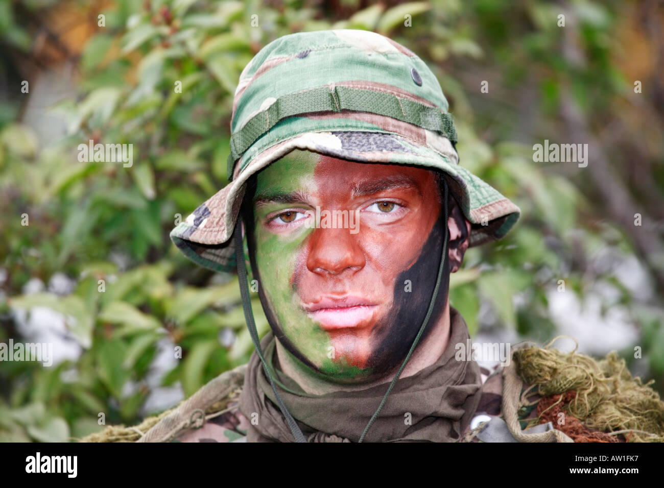 Portrait of a young soldier, recruit with facial camouflage - Stock Image