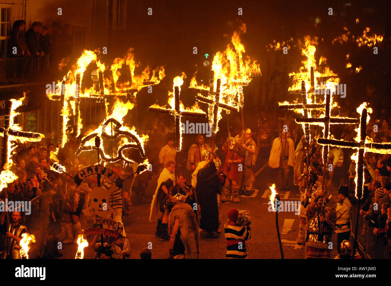 Burning crosses form part of a breathtaking parade of fire and fireworks on bonfire night in Lewes, England. - Stock Image