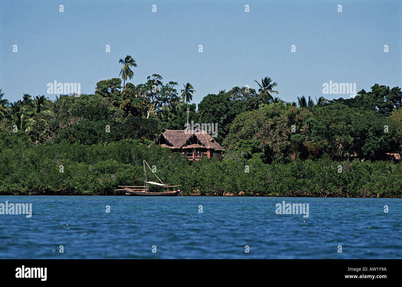 View of one of the Chole Mjini lodge buildings beyond a dhow Chole island is located adjacent to Mafia island Tanzania - Stock Image